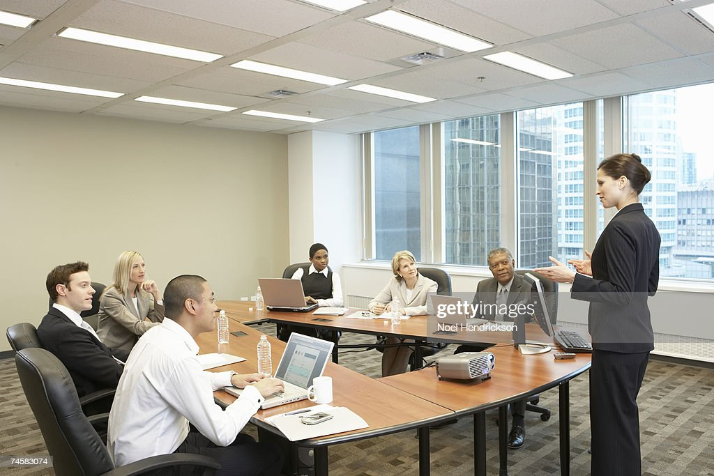 Group of business people sitting at table in conference room, one woman standing, side view : Stock-Foto