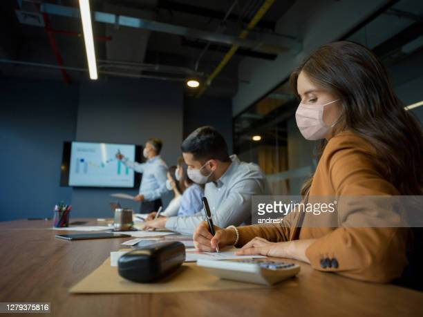 group of business people social distancing at the office and wearing facemasks - biosecurity stock pictures, royalty-free photos & images