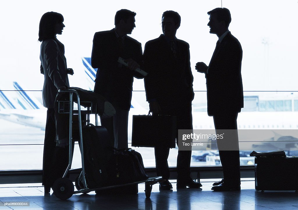 Group of business people standing inside airport, silhouette. : Stockfoto