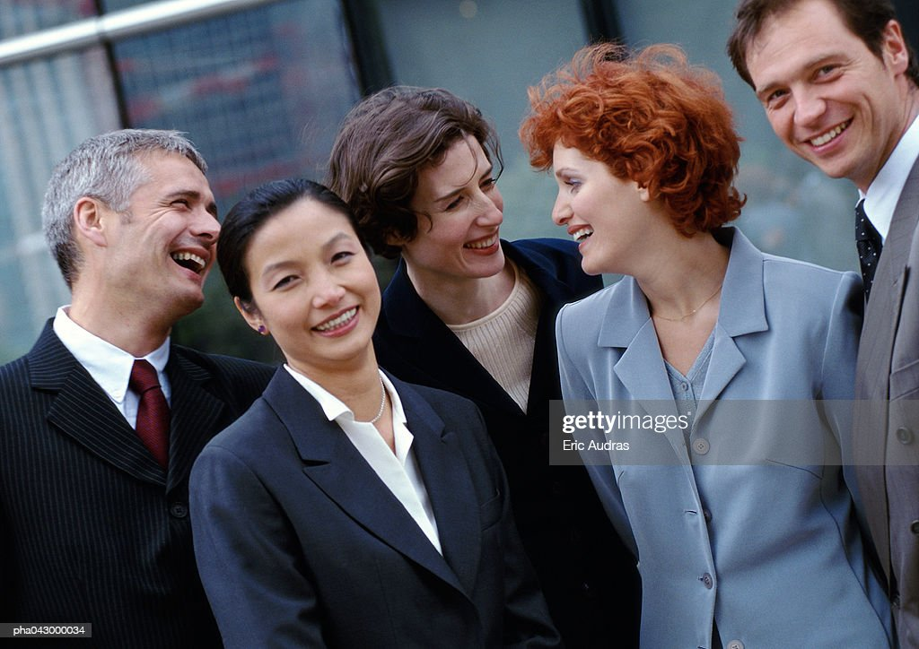 Group of business people standing side by side, smiling : Stockfoto