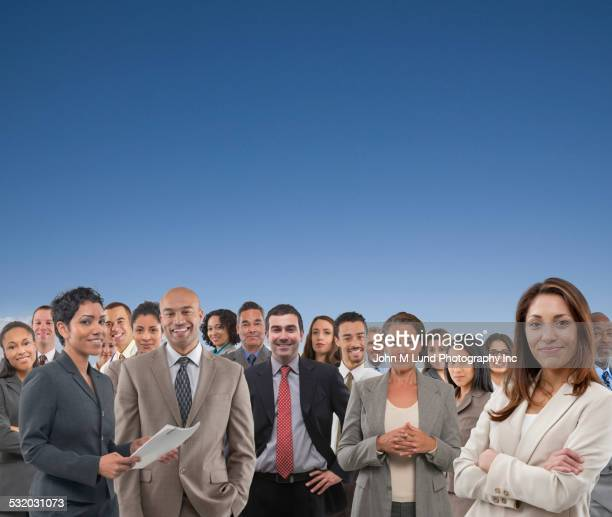 Group of business people standing under blue sky
