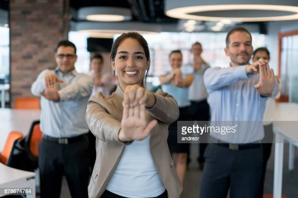 Group of business people stretching while taking a break from work at the office