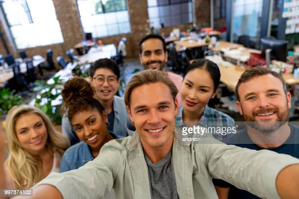 group of business people taking a selfie at the office - customer engagement stock pictures, royalty-free photos & images