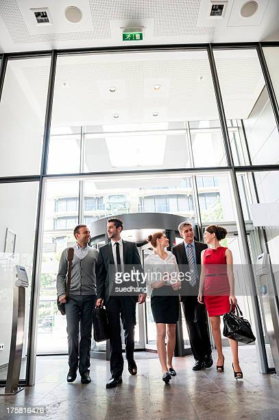 Group of business people talking and entering into glass office building