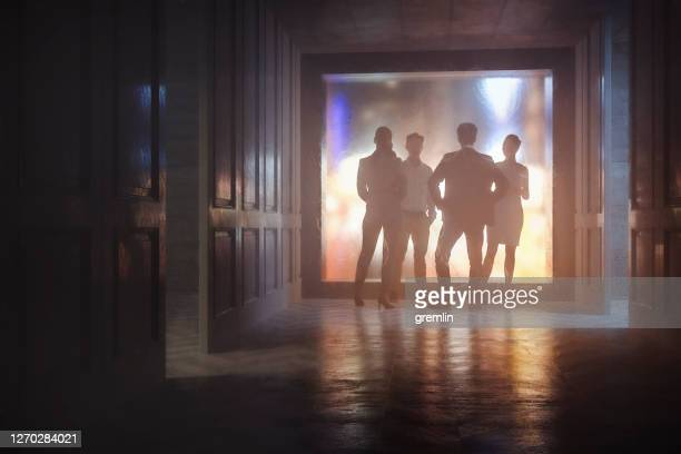 暗闇の中で話すビジネスマンのグループ - 陰謀 ストックフォトと画像