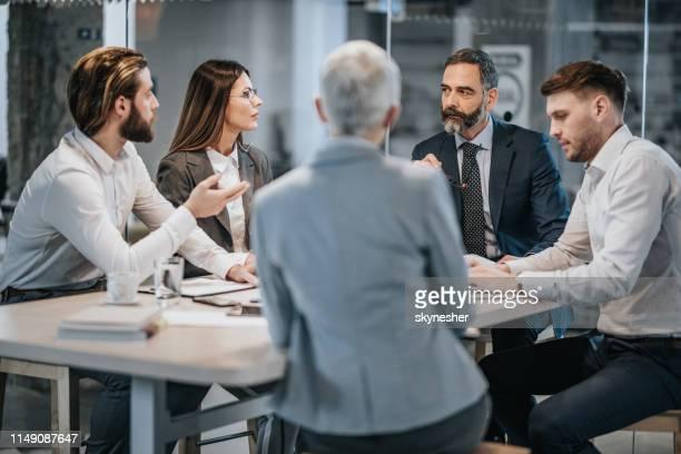 grupo de executivos que falam em uma reunião no escritório. - reunião de equipe - fotografias e filmes do acervo