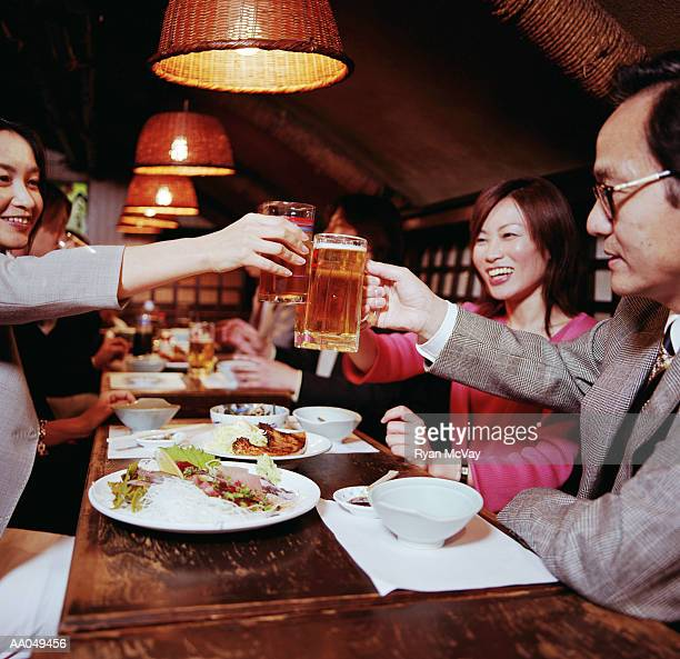 Group of business people toasting mugs of beer over dinner
