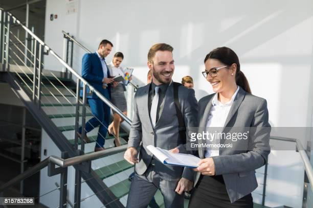 Groupe de gens d'affaires à pied dans les escaliers et communiquer