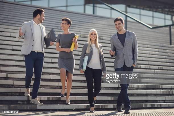 Groupe de gens d'affaires en descendant les escaliers et souriant.