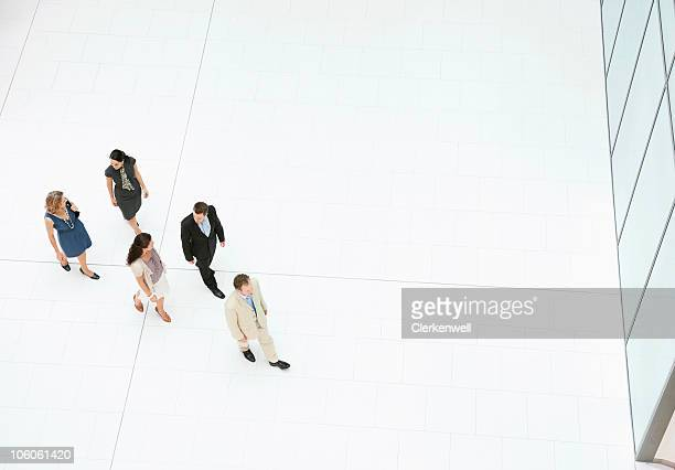 group of business people walking in modern office building - following stock pictures, royalty-free photos & images
