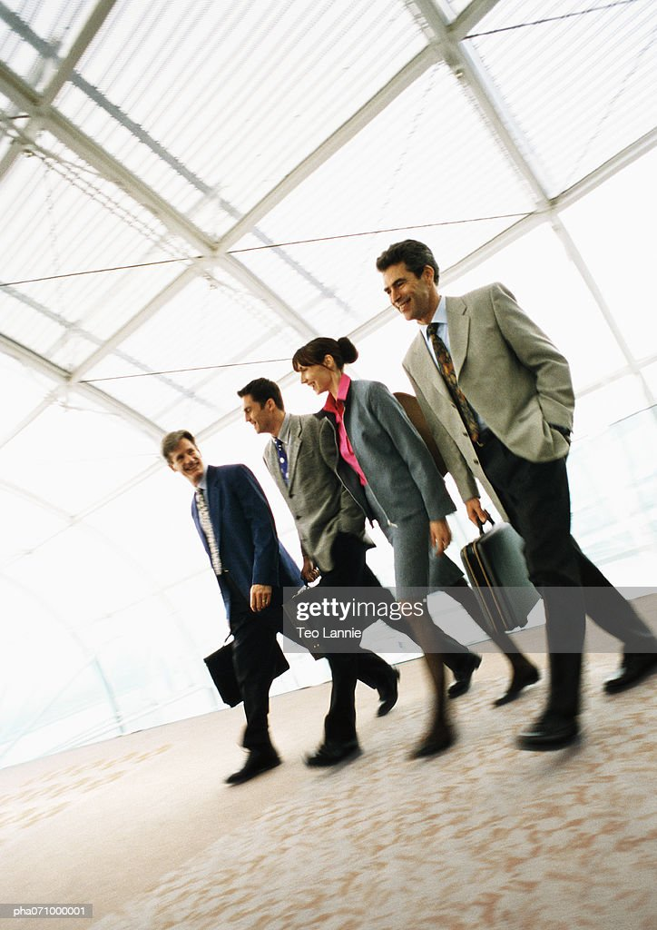 Group of business people walking inside with briefcases. : Stockfoto
