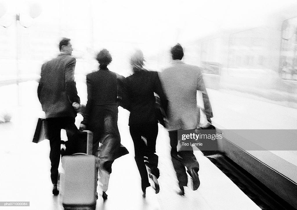 Group of business people walking near train, rear view, blurred, b&w. : Stockfoto