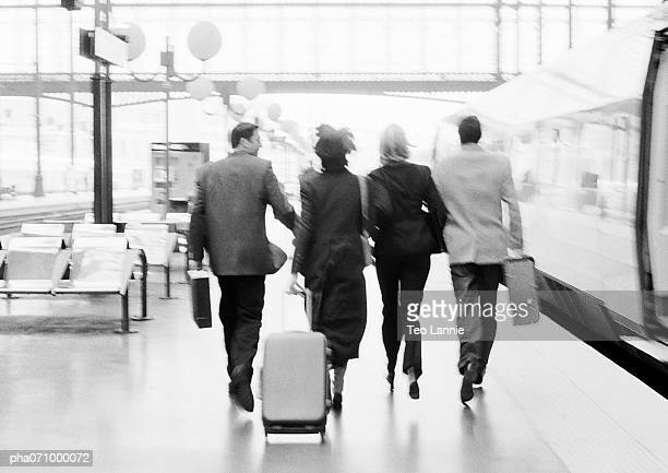 Group of business people walking next to train in station, rear view, b&w.