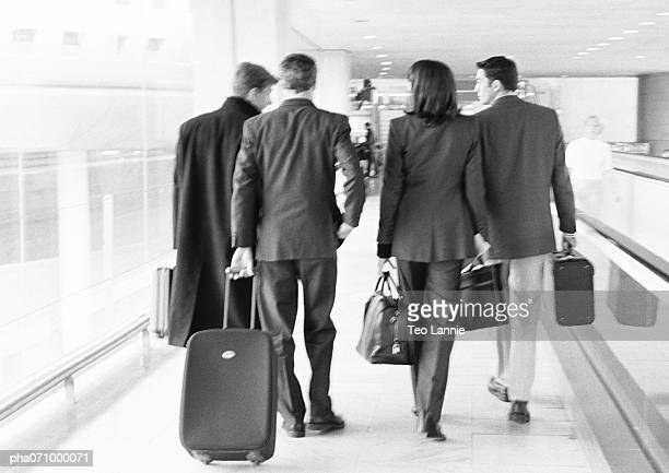 Group of business people walking through terminal, full length, rear view, b&w.