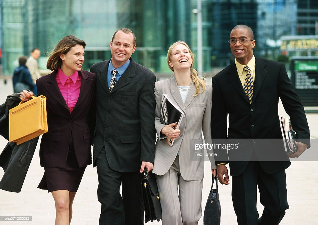 Group of business people walking together outside, three quarter length, front view : Stockfoto