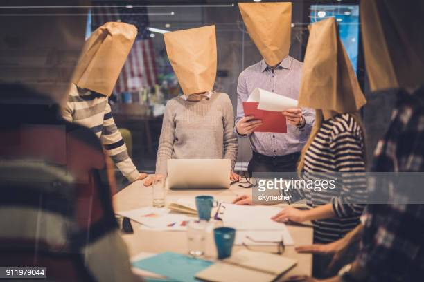 Group of business people with paper bags having a meeting in the office.
