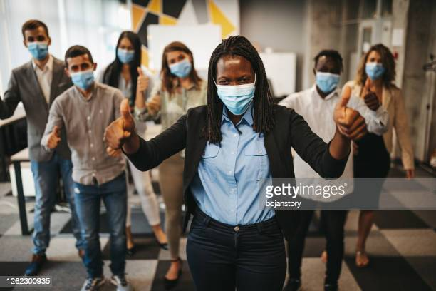 group of business people with protective face masks celebrating success - medium group of people stock pictures, royalty-free photos & images
