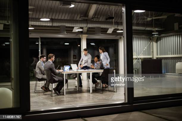 group of business people working on computers late in the office. - input device stock photos and pictures
