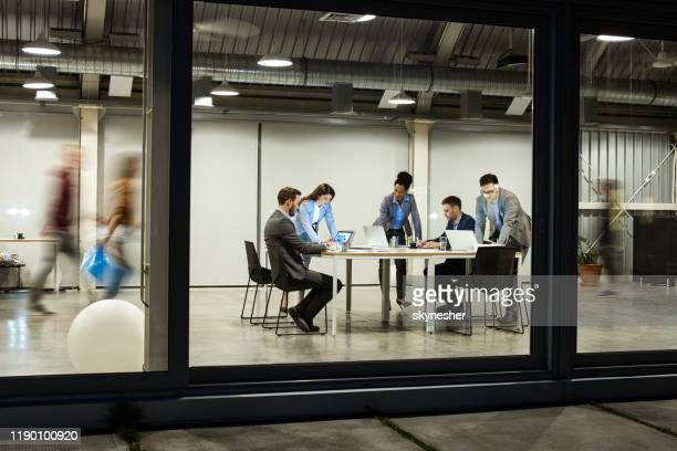 group of business people working on computers late in the office. - smart casual stock pictures, royalty-free photos & images
