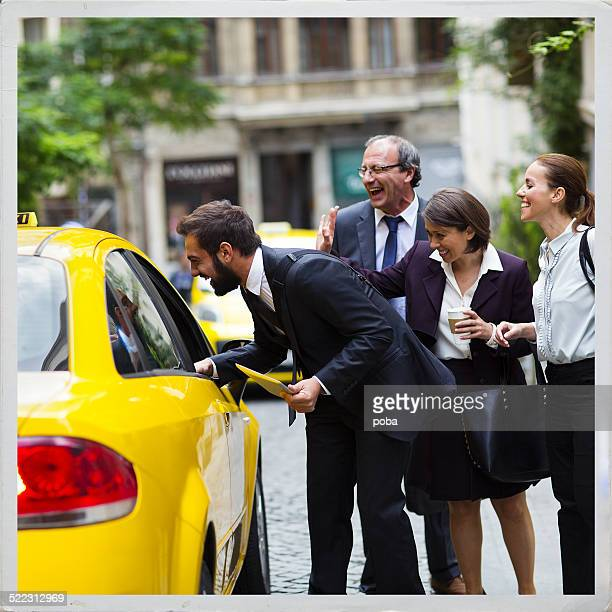 group of business peoplel hailing a yellow Taxi cab