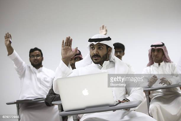 A group of business students one using an Apple Inc laptop computer raise their hands to answer questions from a lecturer during a lesson at the...