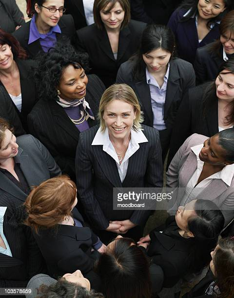 Group of business women looking at woman standing in middle, elevated view