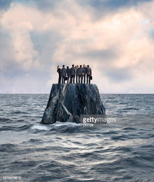 group of businessman and businesswoman stand on isolated island in ocean - remote location stock pictures, royalty-free photos & images