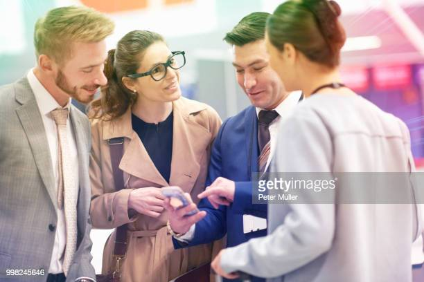 Group of businessmen and women standing, catching up, businessman looking at smartphone