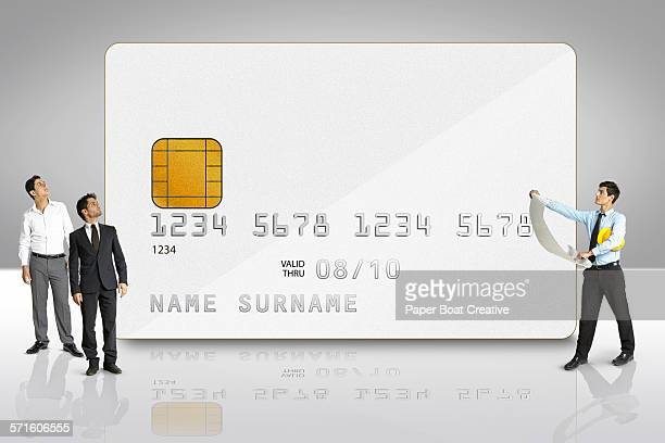 group of businessmen by a giant silver credit card