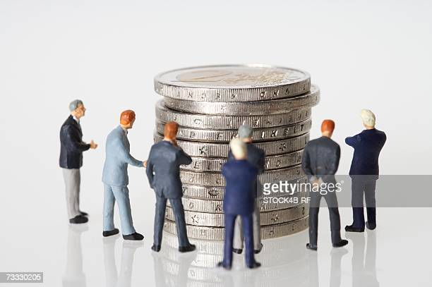 Group of businessmen figurines around a stack of coins