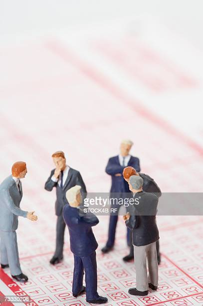 Group of businessmen figurines standing on a lottery ticket