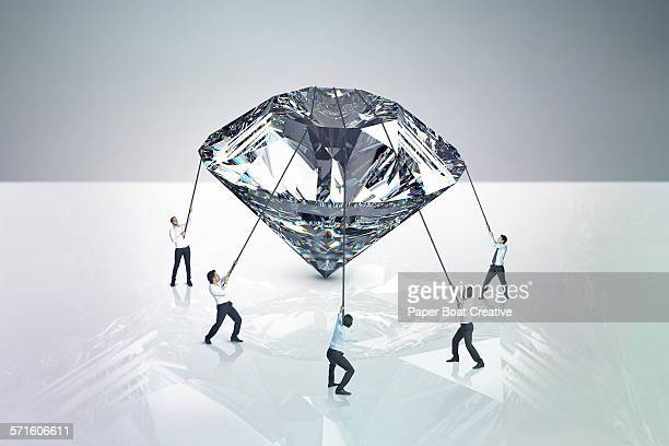 Group of businessmen holding a giant diamond
