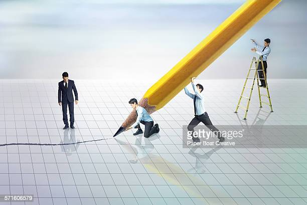 group of businessmen holding a giant pencil