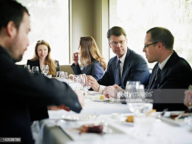 Group of businessmen in discussion during lunch
