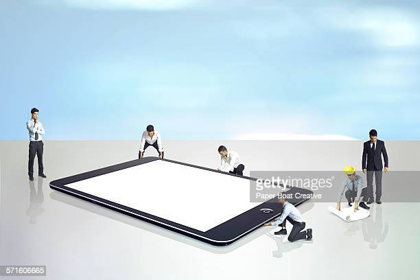 Group of businessmen looking at a giant ipad