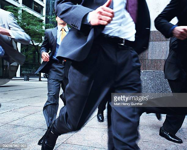 Group of businessmen running from building