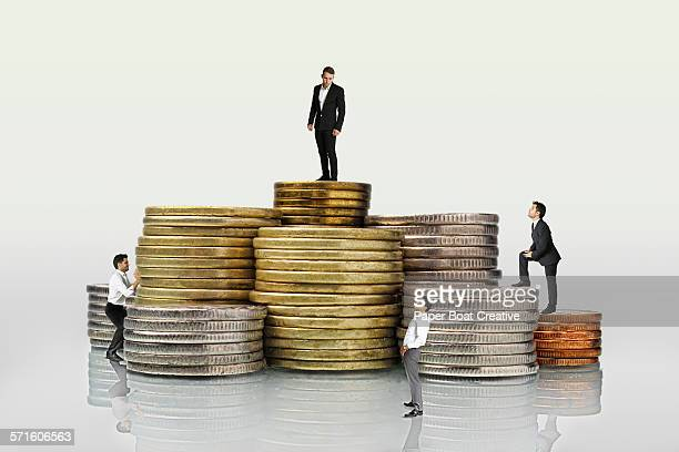 Group of businessmen standing on different coins