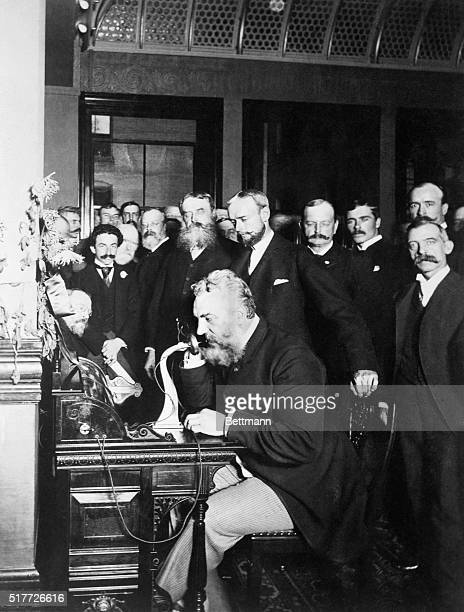 A group of businessmen watch inventor Alexander Graham Bell as he opens the New YorkChicago telephone line