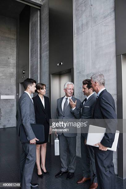 Group of businesspeople discussing at elevator