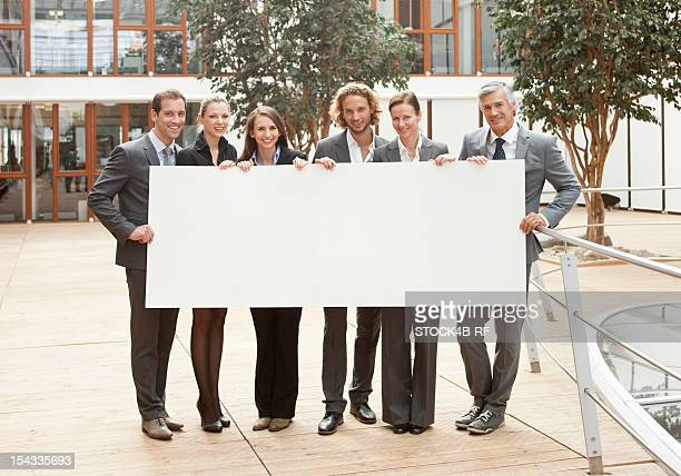 Group of businesspeople holding blank sign