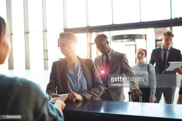 group of businesspeople in queue at counter in airport - register stock photos and pictures