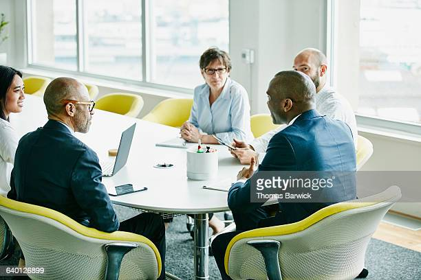 group of businesspeople in team meeting in office - african american man helping elderly stock pictures, royalty-free photos & images