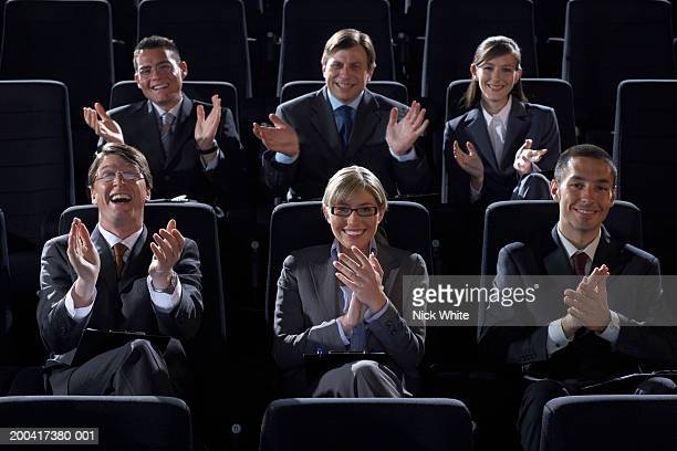 Group of businesspeople in theater clapping, smiling, portrait