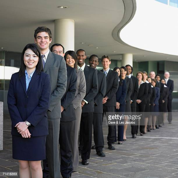 Group of businesspeople lined up in front of a building