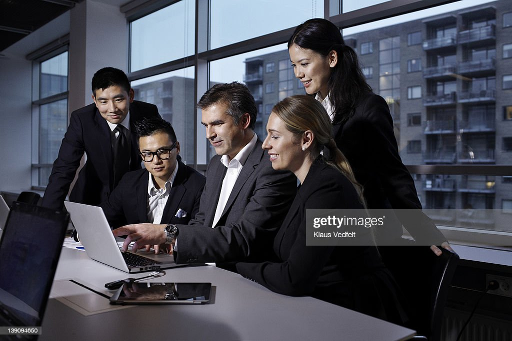 Group of businesspeople looking at laptop : Stock Photo