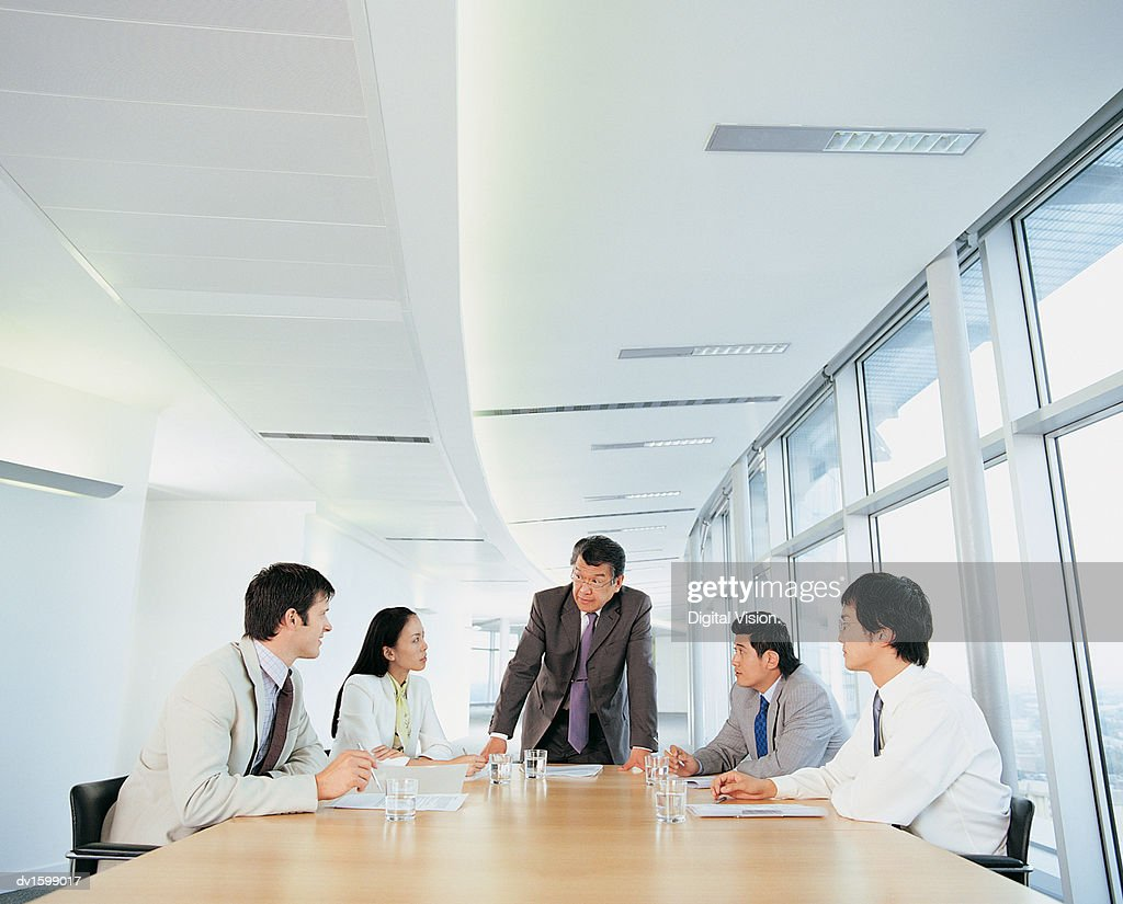 Group of Businesspeople Planning Strategy all Looking at One Man : Stock Photo