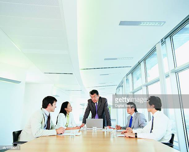 Group of Businesspeople Planning Strategy at a Conference Table in a Narrow Office Corridor