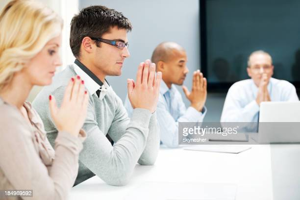 Group of businesspeople pray in a office.