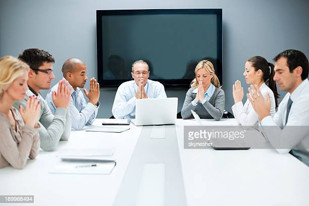 Group of businesspeople pray on a meeting.