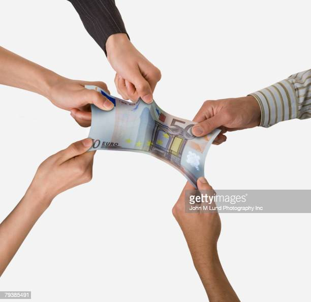 Group of businesspeople pulling on money